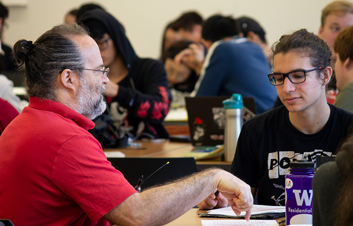 professor adler works with student in class